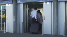 Young couple entering elevator at the airport, business trip, travel and tourism