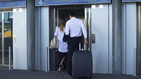 Young couple entering elevator at airport, business trip, travel and tourism. Stock footage Royalty Free Stock Images