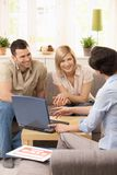 Young couple with estate agent. Young couple having appointment with estate agent in sunny living room stock images