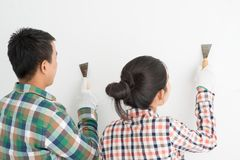 Couple remodeling house. Young couple even out wall with spatulas Stock Image