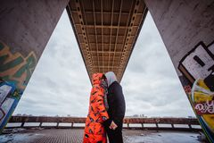 Young couple in the evening under the bridge. Young loving couple walking in the city under the bridge close Royalty Free Stock Photos