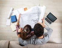 Young couple examining blueprints Stock Photo
