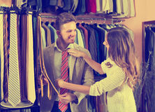 Young couple examining various ties. In men's cloths store Stock Photos