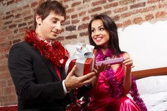 Young couple exchanging gifts Royalty Free Stock Photo