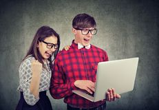 Young couple excited with win using laptop stock photography