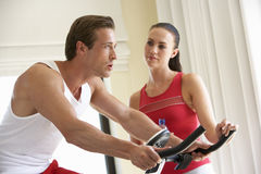 Young Couple On Exercise Bike Royalty Free Stock Photos