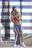 Young couple in exercise clothes, man embracing woman. Young couple in exercise clothes, men embracing woman stock photos