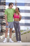 Young couple in exercise clothes, smiling at each other stock images