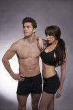 Young couple exercise together. Young fitness couple in the studio Stock Photos