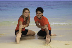 Young couple exercising on a beach Royalty Free Stock Images