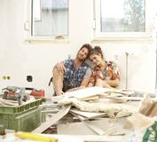 Young couple exhausted in DIY. Young couple sitting exhausted in house under construction among construction waste, smiling royalty free stock image