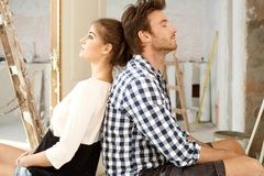 Young couple exhausted in DIY. Young couple sitting on floor exhausted in renewing house. Sitting back to back Stock Image