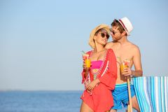 Young couple with exotic cocktails on beach. Space for text stock photo