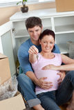 Young couple expecting a baby, on floor with key Royalty Free Stock Image