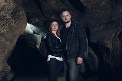 Young couple exploring huge cave. Adventure travellers dressed cowboy hat and backpack, leather jacket. extreme vacation, tourist royalty free stock photo