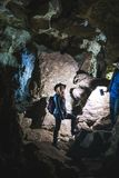 Young couple exploring huge cave. Adventure travellers dressed cowboy hat and backpack, leather jacket. extreme vacation, tourist stock photo