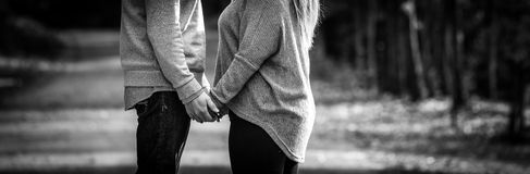 Young couple facing each other while holding hands, black and white, expressing love, Royalty Free Stock Images