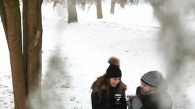 A young couple in a fairy-tale winter is warmed by a warm drink stock video footage