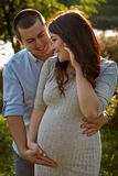 Couple family in the expectation of a baby hugging in sun rays. Young couple family in the expectation of a baby hugging in the park in sun rays Royalty Free Stock Photo