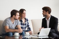 Young couple, family at meeting with realtor, interior designer. Decorator, landlord. Employee consulting, showing sketches on laptop. Concept of meeting with stock image