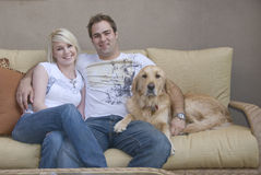 Young couple with Family pet. Attractive young couple and their Golden Retriever dog sitting on sofa Stock Image