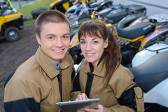 Young couple farmers discussing about new tractors stock image