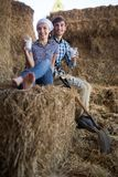 Couple of farmers drinking milk in hayloft on farm. Young couple of farmers drinking milk in hayloft on farm Royalty Free Stock Images