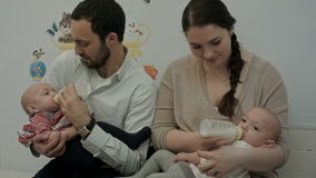 Young couple feed newborn twins from a bottle stock video