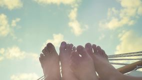 Young couple feet rest in hammock on the sky background in slwomotion. 1920x1080. hd stock video footage