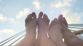 Young couple feet rest in hammock on the sky background in slwomotion. 1920x1080 stock footage