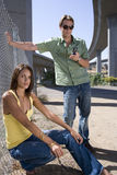 Young couple by fence beneath overpass, man using mobile phone, portrait of woman Royalty Free Stock Photography