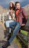 Young Couple on Fence in Mountains Royalty Free Stock Images
