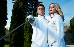 Young couple in fencing costumes Stock Image