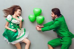 Young couple in festive costumes saint patrick`s day top view giving present. Young couple wearing festive costumes saint patrick`s day top view isolated on grey Stock Image