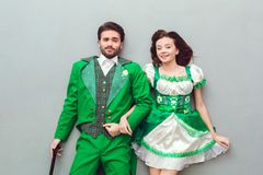 Young couple in festive costumes saint patrick`s day top view holding hands. Young couple wearing festive costumes saint patrick`s day top view isolated on grey Stock Images
