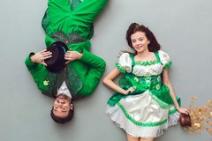 Young couple in festive costumes saint patrick`s day top view upside dow. Young couple wearing festive costumes saint patrick`s day top view isolated on grey Royalty Free Stock Photo