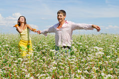 Young couple on field of flowers. In sunny day Stock Photography