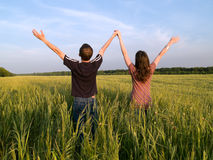 Young Couple in Field Holding Hands Up Stock Image