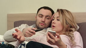 Young couple fighting, arguing in bed at night because woman texting someone using smartphone stock footage