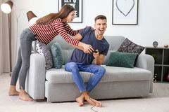 Young couple fighting for joystick while playing video games Stock Image