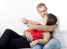 Young couple fighting over remote control Stock Images