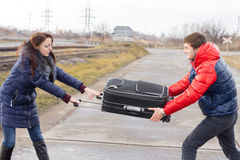 Young couple fighting over a suitcase Stock Images