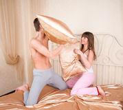 Young couple fighting pillows Stock Images