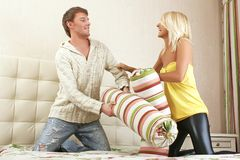 Young couple fighting with pillows royalty free stock photo