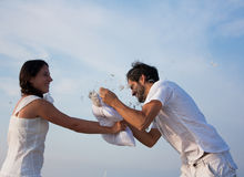 Young couple fighting pillows on the beach Royalty Free Stock Image