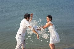 Young couple fighting pillows on the beach Stock Photos