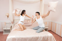 Young couple fighting pillows on bed Stock Images