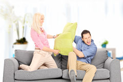 Young couple fighting with pillows at home Stock Photos