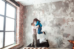 Young couple fighting pillows in the loft style bedroom Royalty Free Stock Photos