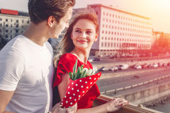 Young couple on first date in sunset. Men surprise with bouquet Royalty Free Stock Images